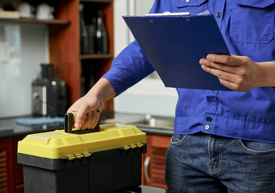 Close-up of repairman standing in uniform with toolbox and holding clipboard, he finished his work in domestic kitchen in apartment
